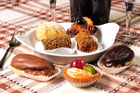 pastries chocolate and fruits on the table with glass and bottle photo