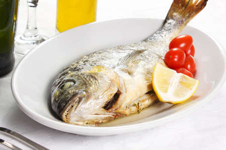 Mediterranean seafood concept  Sea bream on white plate with fresh herbs and colorful peppercorns on white background  Luxuus fish eating  Stock Photo - 17720554
