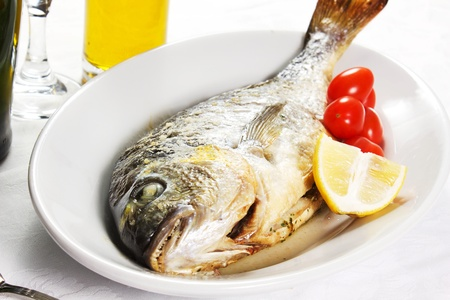 Mediterranean seafood concept  Sea bream on white plate with fresh herbs and colorful peppercorns on white background  Luxurious fish eating  Stock Photo - 17720557