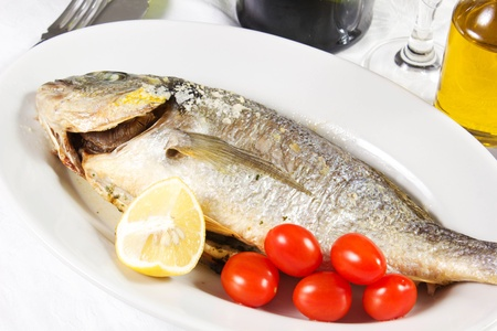Mediterranean seafood concept  Sea bream on white plate with fresh herbs and colorful peppercorns on white background  Luxurious fish eating Stock Photo - 17720586
