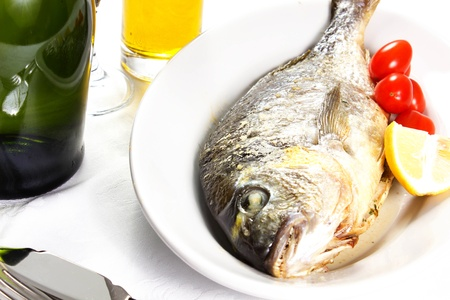 Mediterranean seafood concept  Sea bream on white plate with fresh herbs and colorful peppercorns on white background  Luxurious fish eating Stock Photo - 17720587