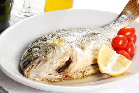 Mediterranean seafood concept  Sea bream on white plate with fresh herbs and colorful peppercorns on white background  Luxurious fish eating  Stock Photo - 17720553