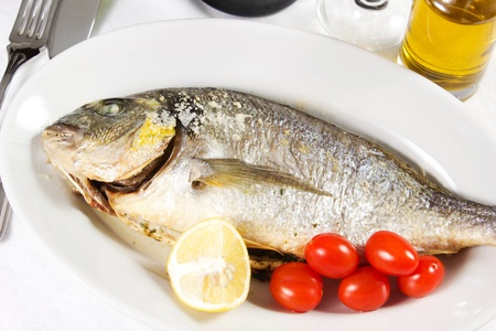 Mediterranean seafood concept  Sea bream on white plate with fresh herbs and colorful peppercorns on white background  Luxurious fish eating  Stock Photo - 17720597
