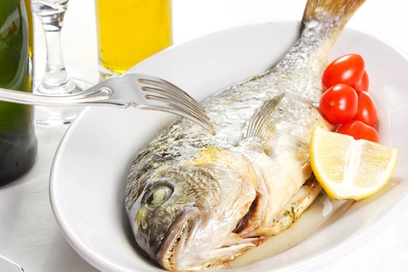 Mediterranean seafood concept  Sea bream on white plate with fresh herbs and colorful peppercorns on white background  Luxurious fish eating  Stock Photo - 17720547
