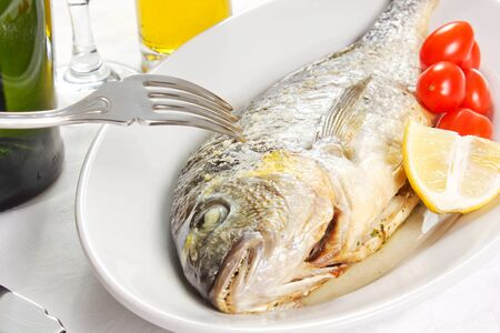 Mediterranean seafood concept  Sea bream on white plate with fresh herbs and colorful peppercorns on white background  Luxurious fish eating Stock Photo - 17720574