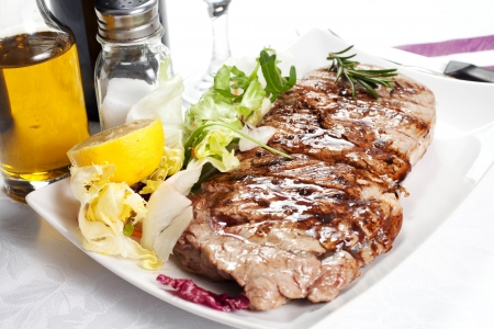 t bone: bovine meat cooked on the griddle in the dish on the table with oil and salt Stock Photo