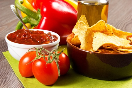 chips and salsa: nachos on the table with tomatoes, pepper and oil