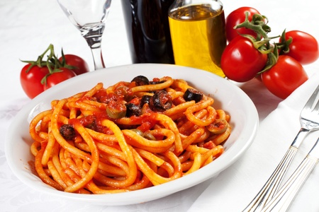 pasta with olives, bacon and sauce on the table with wine, oil and tomatoes photo