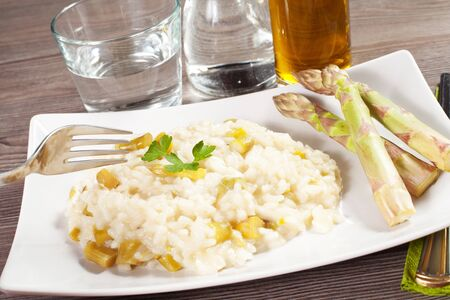 rice with asparagus on a wood table with water and oil Stock Photo - 18810285
