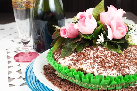 campagne: chocolate cake with pink rose on the wood table with campagne Stock Photo
