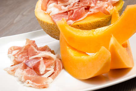 Ham and melon on the white dish on a wood table