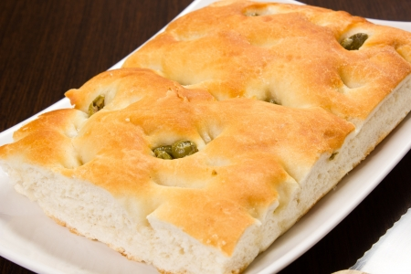 Focaccia with green olives, focaccia is flat oven baked Italian bread on the wood table with knife