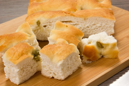 focaccia with green olives, focaccia is flat oven baked Italian bread on the wood table photo