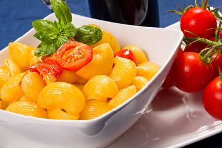 pasta with fresh tomatoes in the dish on the blue tablecloth photo