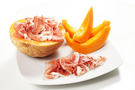 Ham and melon on white background