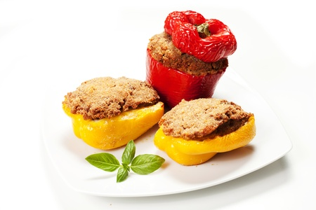 Stuffed peppers with basil on the dish on the white background photo