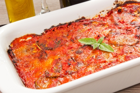 eggplants parmigiana traditional italian recipe on the wood table with oil Stock Photo