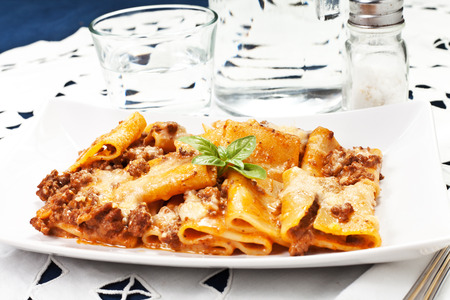 pasta with bechamel and meat sauce and tomatoes on the table photo