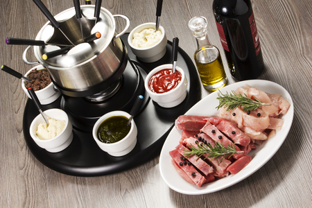 Fondue skewer with meat, on the table with sauce