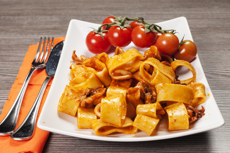 sauced pasta with squid on the wooden table photo