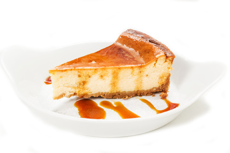cheesecake with caramel sauce on the white background