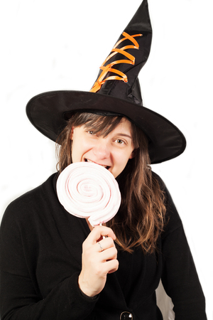 Beautiful girl witch casts a spell over pumpkins. Halloween. Isolated over white. photo