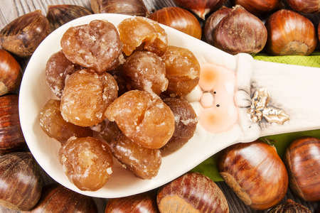 Chestnuts and marron glace over a light brown background photo