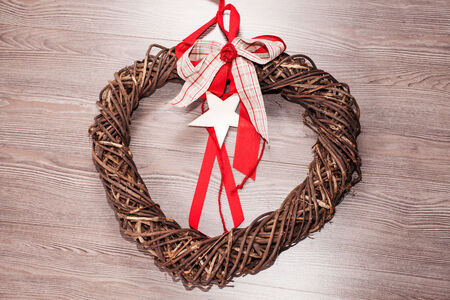 Closeup of heart-shaped Christmas or St. Valentine wicker wreath with red felt. Square crop isolated on white photo