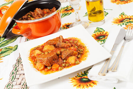 ailment: Beef stew with potatoes, carrots and peas on the tablecloth