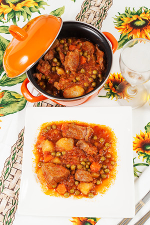 Beef stew with potatoes, carrots and peas on the tablecloth