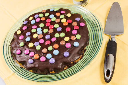 chocolate cake with smarties on the yallow tablecloth Stock Photo