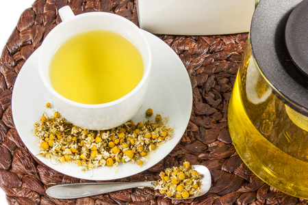 nature cure: Chamomile tea with chamomile flower on the white background