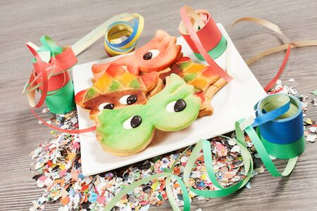 Carnival cookies with streamers and confetti on the wood table