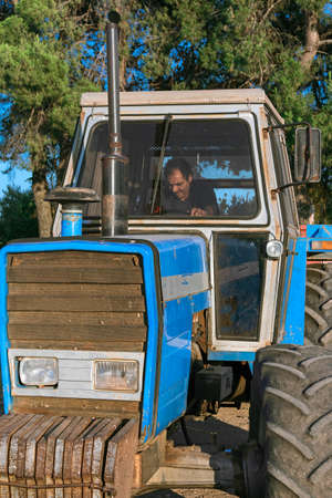 manage transportation: Man driving farm tractor