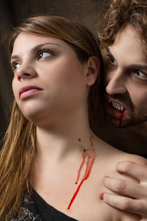 wolf couple: vampire bites the neck of a girl Stock Photo