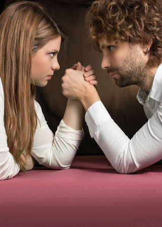 challenging sex: competition between man and woman on pink table Stock Photo