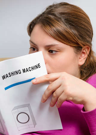 instruction: housewife reads instruction booklet of washing machine Stock Photo