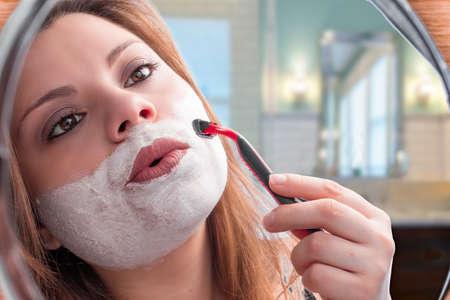 gay girl: girl in the mirror shaving with razor