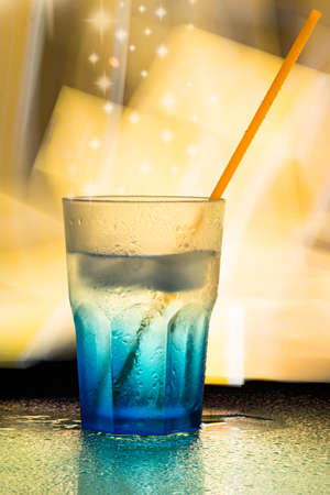 sopping: blue wet glass with orange straw Stock Photo
