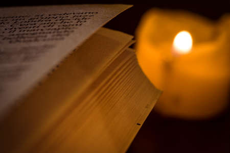 book pages illuminated by candle Stock Photo