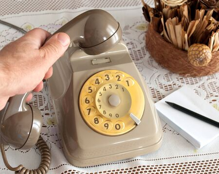 vintage telephone with hands on white background photo