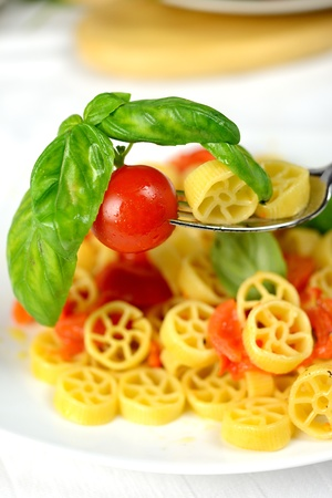 wheels of pasta with fresh tomatoes and basil oil photo