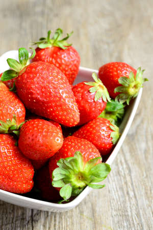 strawberies: cup of fresh and natural strawberries on wooden table