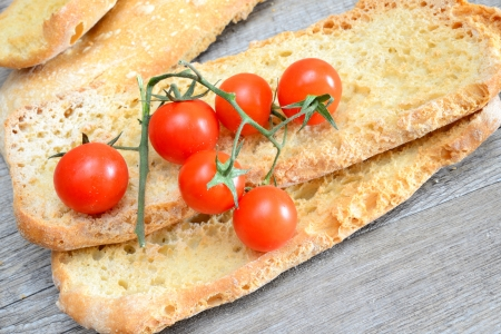 be soaked: dried bread called freselle, soaked in the water to be served with olive oil and sliced tomato Stock Photo
