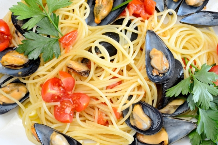 spaghetti pasta with mussels with fresh tomato olive oil and parsley Stock Photo