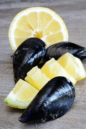 pieces of raw mussels with lemon and parsley on wooden table Stock Photo - 20447999