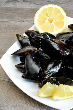 pieces of raw mussels with lemon and parsley on wooden table Stock Photo - 20448001