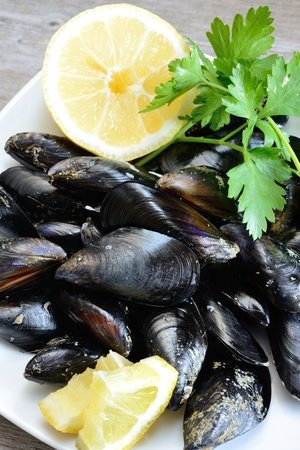 pieces of raw mussels with lemon and parsley on wooden table Stock Photo - 20448022