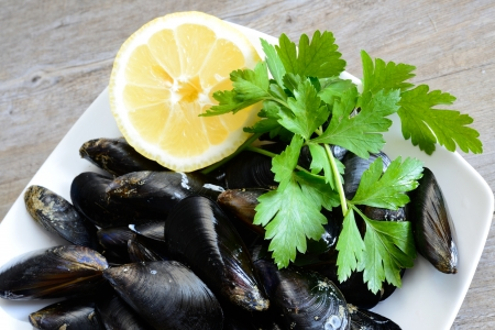 pieces of raw mussels with lemon and parsley on wooden table Stock Photo - 20447991