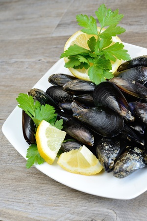 pieces of raw mussels with lemon and parsley on wooden table Stock Photo - 20447992